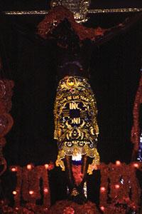 Le Christ sur la croix noirci par la fumée des bougies.