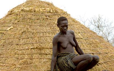 Une femme Bodi achève le toit de sa hutte