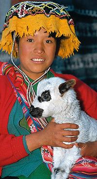 Enfant avec un bébé lama  au Pérou