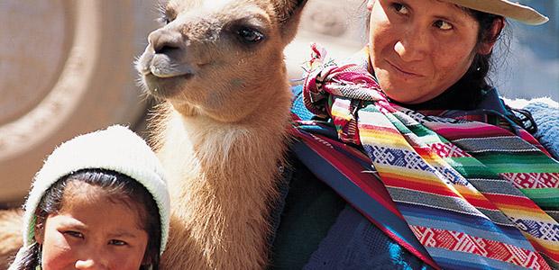 Une femme et son enfant accompagné de leur lama au Pérou