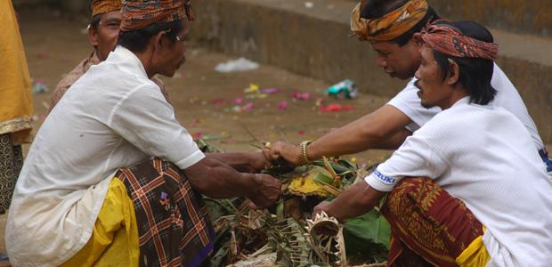 Devant le temple, des hommes préparent les offrandes.